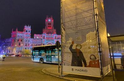 El ángel del edificio Metrópolis de la Gran Vía llena de ilusión la ciudad de Madrid en el instante que llega la estrella de Oriente ante la mirada de un abuelo que pasea con su nieta, cada uno con su mascarilla. Es el cartel ilustrado por Asia Orlando, que podemos ver en numerosos espacios de la ciudad durante las fiestas.