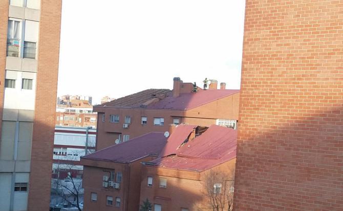 Bomberos retiran la cubierta de un edificio arrancada por el viento, en Villa de Vallecas